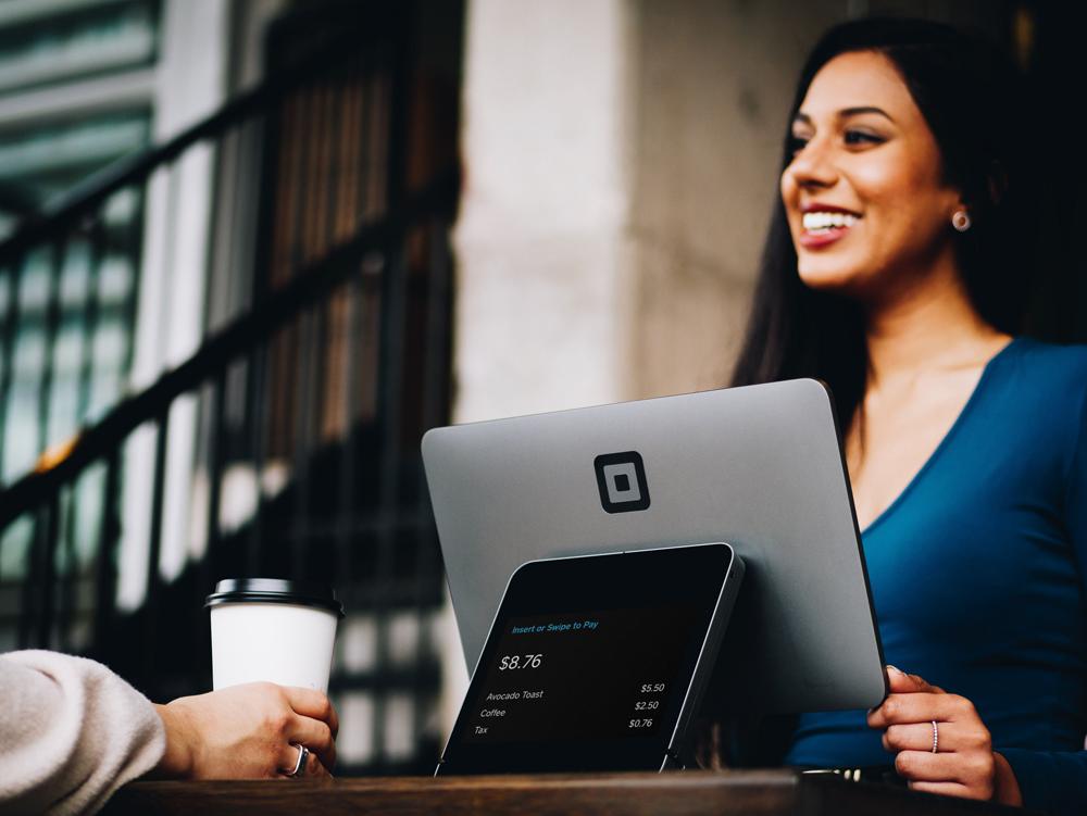 コーヒーを飲みながらパソコンを使っている女性