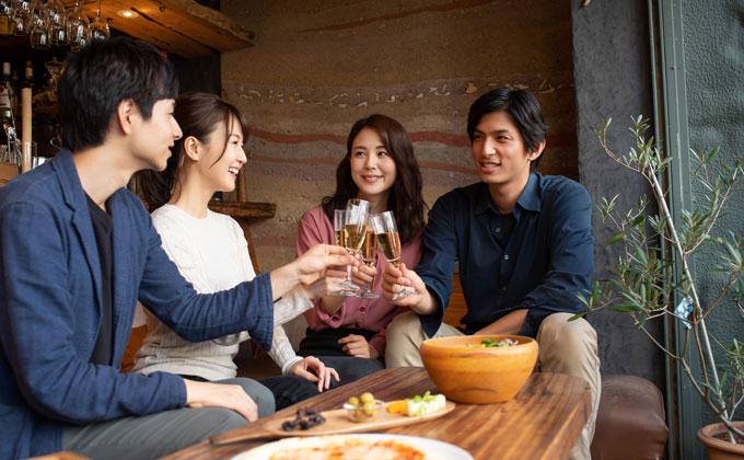 テーブルを囲んで乾杯している男女
