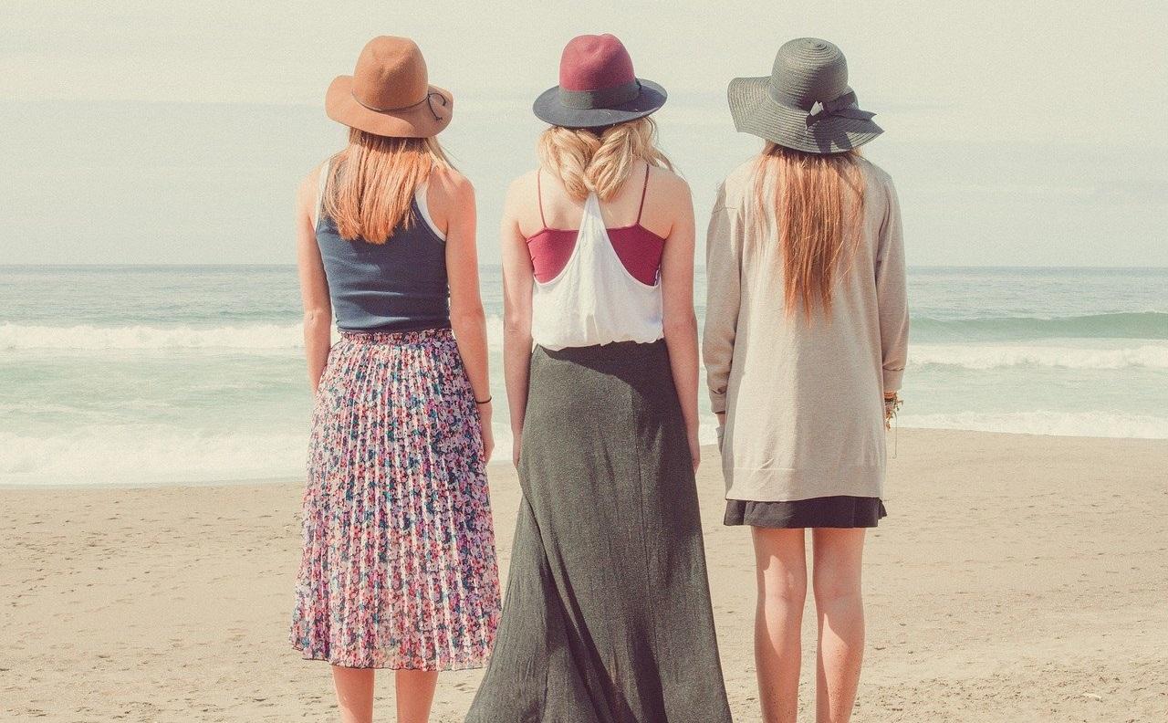 海辺に立っている三人の女性