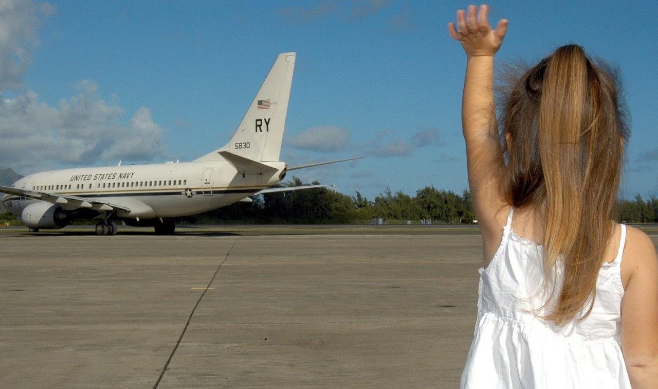 飛行機に手をふる少女