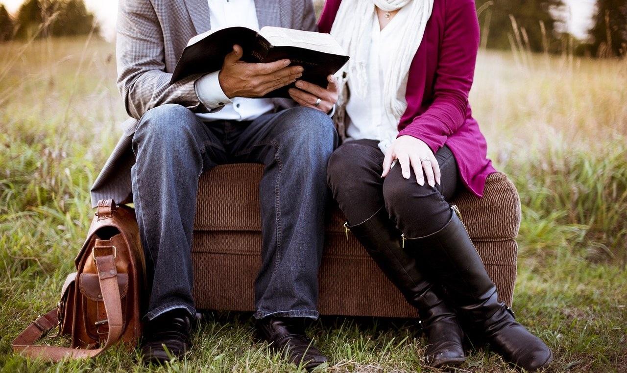 椅子に座って本を読むカップル