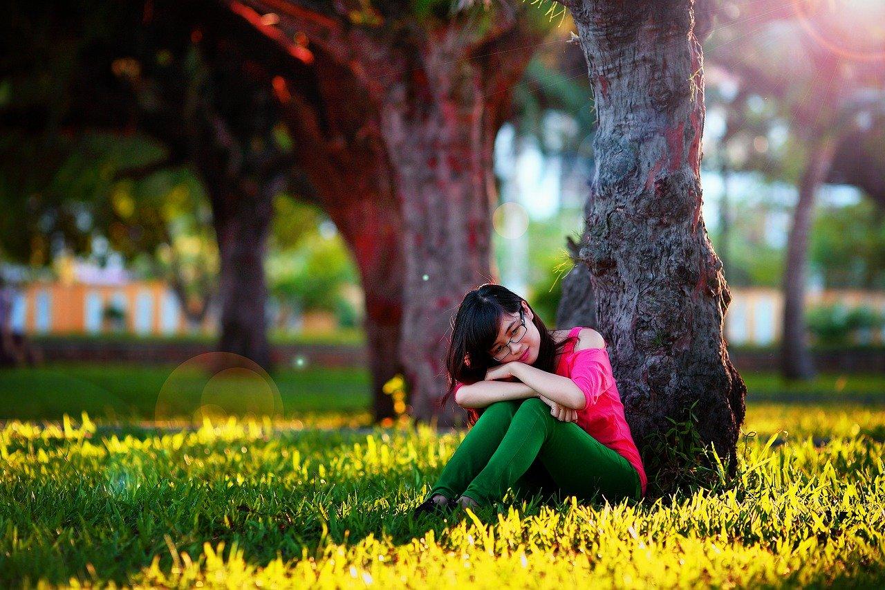 木の下でぼーっとしている女性