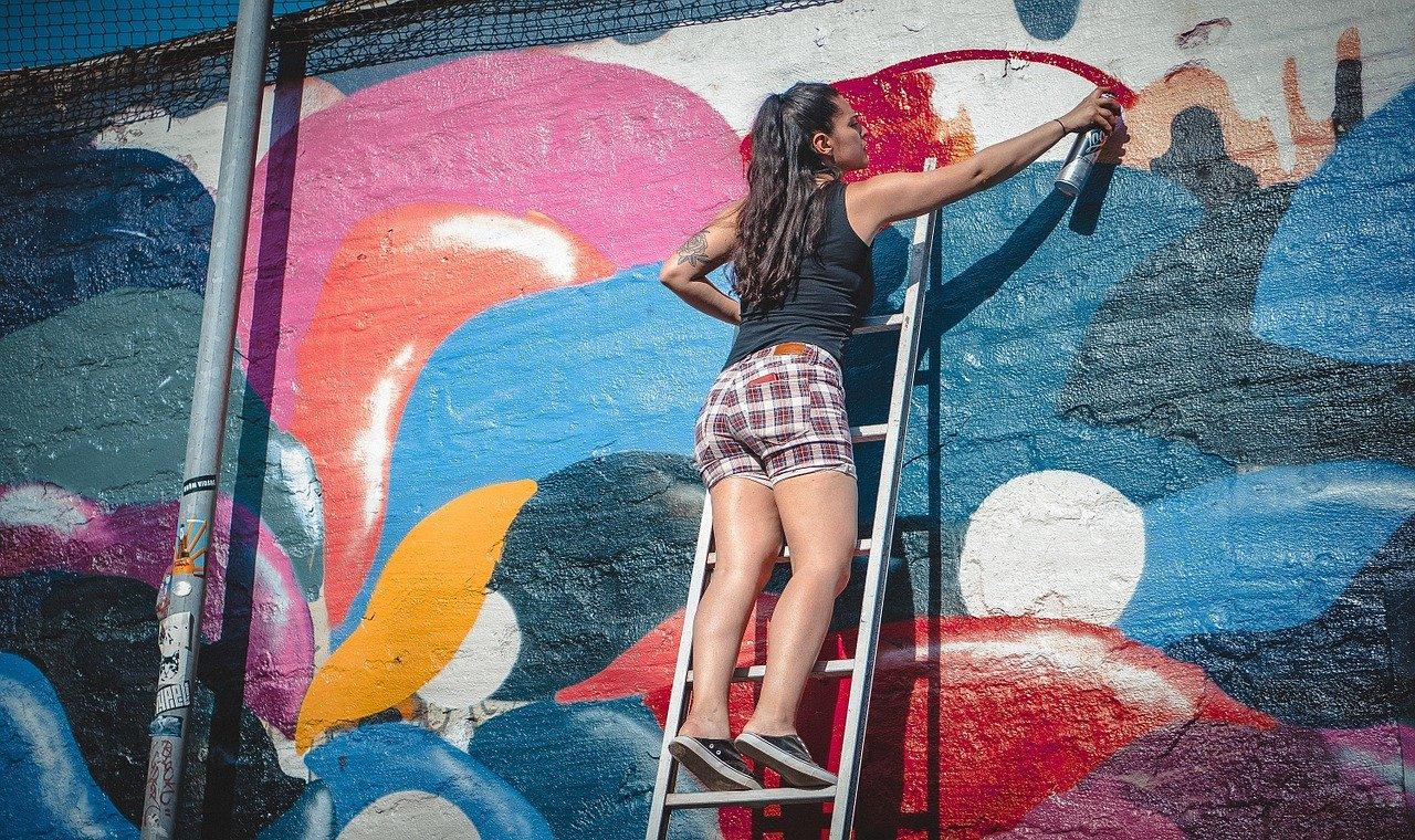 壁に絵を書く女性