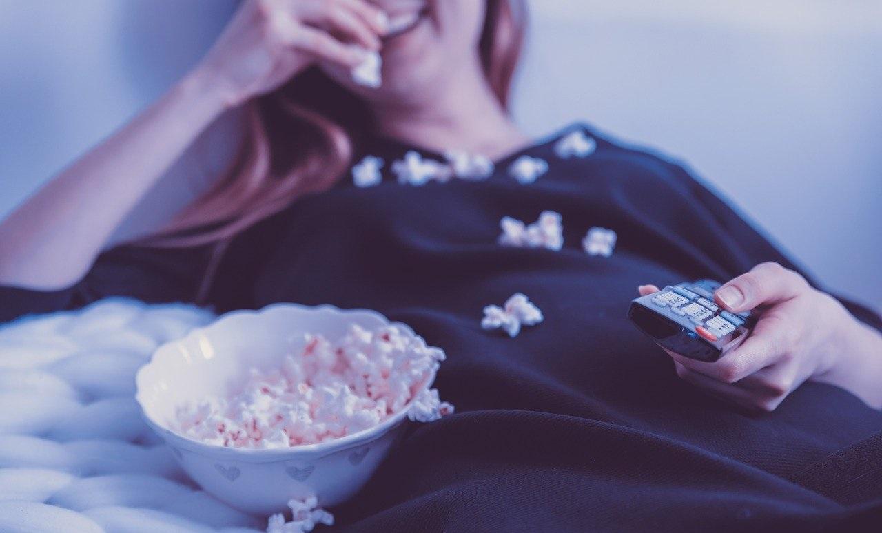 映画を見ながらポップコーンを食べる少女